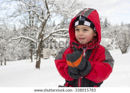 Portrait of a child boy clapping his hands in gloves or mittens in winter in snow. - stock photo