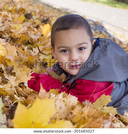 Portrait of a child boy laying on ground, playing in yellow  leaves in autumn or fall. - stock photo
