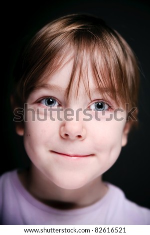 Portrait of a child on a black background. Closeup. - stock photo
