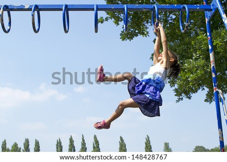 Portrait of a Child Playing and swinging along on Monkey Bars outdoors - stock photo