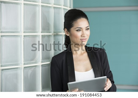 Portrait of a Chinese business woman holding a tablet computer in office. Business woman Looking away thoughtfully. - stock photo