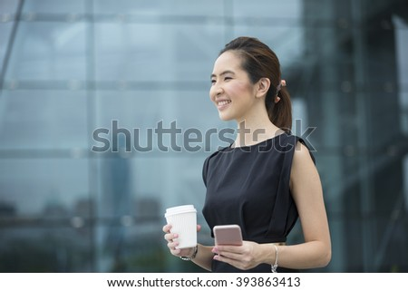 Portrait of a Chinese businesswoman standing outside holding her smart phone. Asian business woman looking away. - stock photo