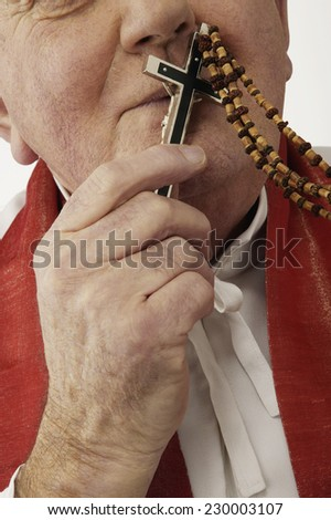 Portrait of a clergyman kissing the cross at the end of rosary beads - stock photo