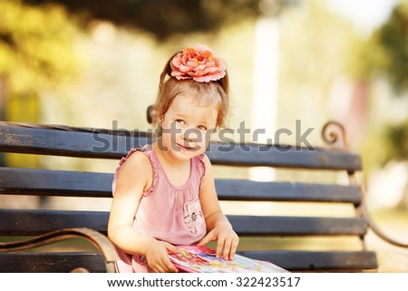 Portrait of a clever little girl reading a children's book on a park bench - stock photo