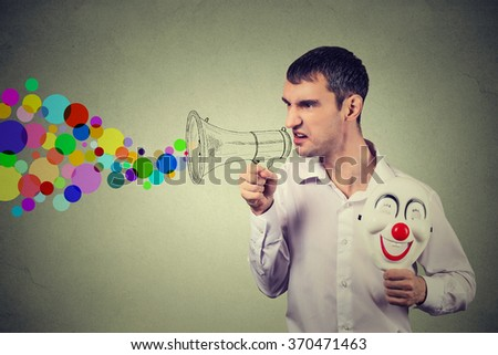 Portrait of a clown young man with mask shouting into a megaphone - stock photo