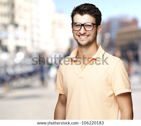 portrait of a comely young man smiling at a crowded street - stock photo