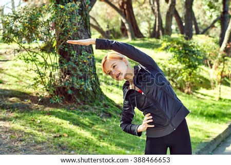 Portrait of a concentrated young pretty woman stretching her arm before jogging in the beautiful green park. - stock photo