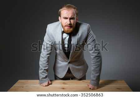 Portrait of a confident angry businessman looking at camera over dark background - stock photo