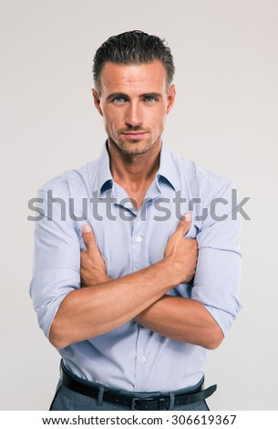 Portrait of a confident businessman standing on gray background and looking at camera - stock photo