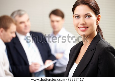 Portrait of a confident businesswoman smiling and looking at camera while his colleagues discussing a project - stock photo
