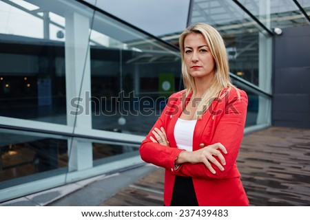 Portrait of a confident businesswoman standing against skyscraper office building, professional businesswoman with arms crossed, successful business woman looking confident - stock photo