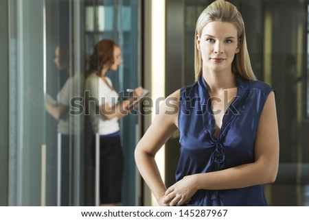 Portrait of a confident businesswoman standing in office corridor with colleague in background - stock photo