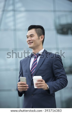 Portrait of a confident Chinese Business man standing in modern city. Business man looking away from camera. - stock photo
