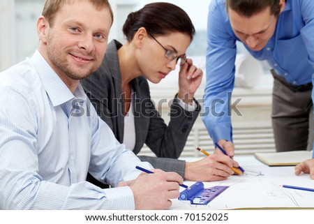 Portrait of a confident engineer against his sketching colleagues - stock photo