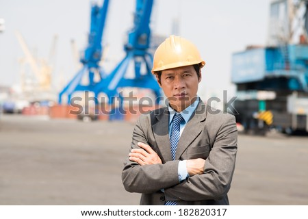 Portrait of a confident inspector looking at camera at port  - stock photo