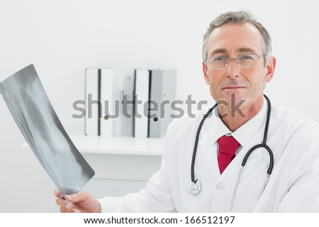 Portrait of a confident male doctor with x-ray picture of lungs in the medical office - stock photo