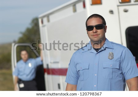 Portrait of a confident male paramedic standing in front of car - stock photo