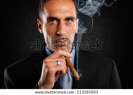 Portrait of a confident man smoking a cigar - stock photo