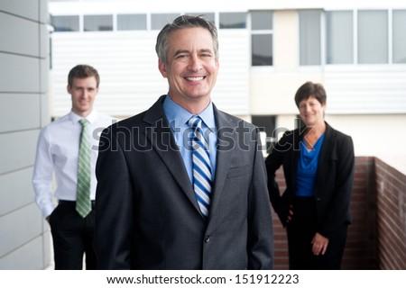 portrait of a confident mature businessman standing outside - stock photo