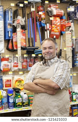 Portrait of a confident middle-aged salesperson with arms crossed in hardware store - stock photo