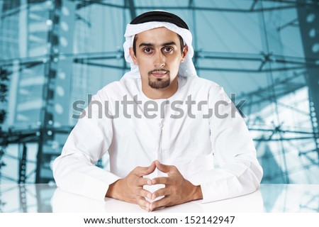 Portrait of a confident Middle Eastern businessman sitting and looking at the camera. - stock photo