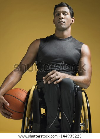 Portrait of a confident paraplegic athlete in wheelchair holding basketball against yellow background - stock photo
