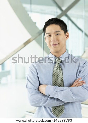 Portrait of a confident smiling businessman standing with arms crossed - stock photo