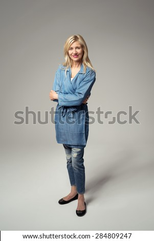 Portrait of a Confident Stylish Blond Woman Standing Against Gray Background with Arms Crossing Over her Stomach and Looking at the Camera. - stock photo