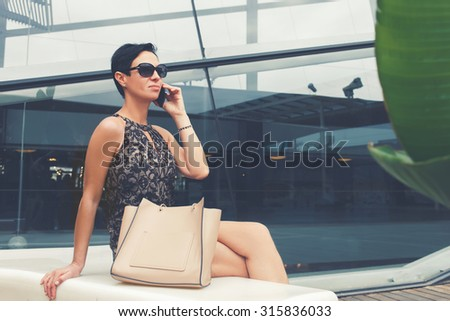 Portrait of a confident woman employed calling with smart phone while resting after work day outdoors, charming female entrepreneur having mobile phone conversation while sitting near office building - stock photo