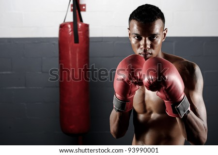 portrait of a confident young boxer in the gym - stock photo