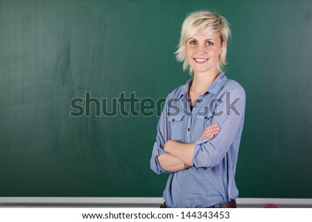 Portrait of a confident young female teacher with arms crossed in front of chalkboard - stock photo