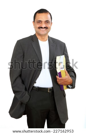 Portrait of a confident young indian business man standing with books - stock photo