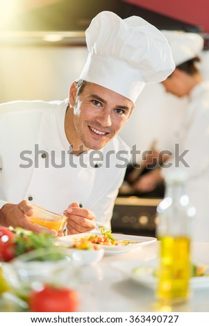 Portrait of a cook chef in his forties. He is looking at camera and about to put sauce on a plateful. He is wearing white chef clothes and hat. Another woman chef is cooking in the blurred  - stock photo