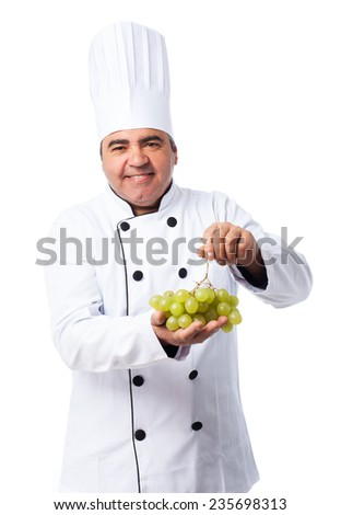 portrait of a cook man holding a grapes bunch - stock photo