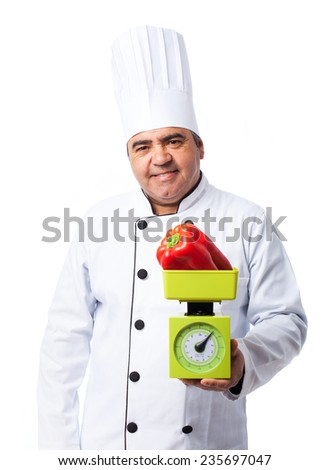 portrait of a cook man weighing a red pepper - stock photo