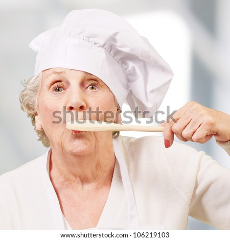 portrait of a cook senior woman with a wooden spoon on a mouth indoor - stock photo