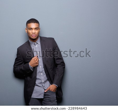Portrait of a cool african american man with black business jacket posing on gray background - stock photo