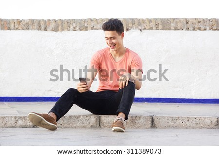 Portrait of a cool guy sitting on sidewalk looking at mobile phone - stock photo