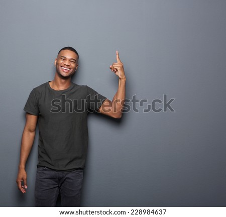 Portrait of a cool guy smiling and pointing finger on copy space gray background - stock photo