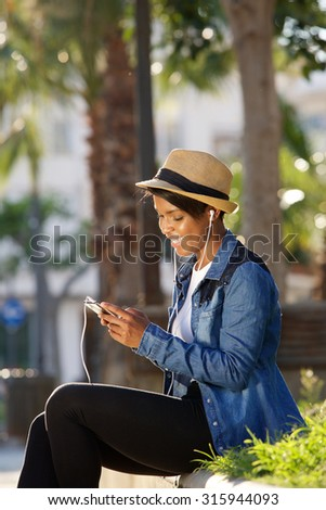 Portrait of a cool young black woman listening to music with earphones - stock photo