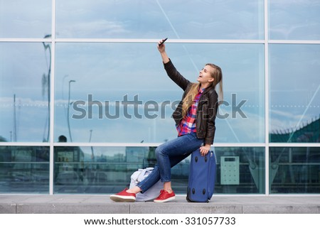 Portrait of a cool young woman taking selfie with travel bags - stock photo
