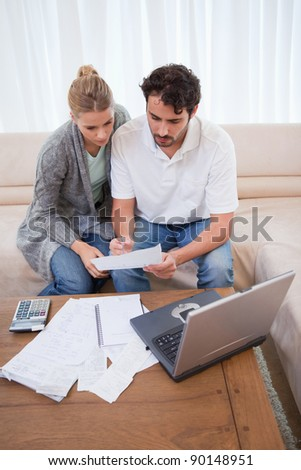 Portrait of a couple doing their accounting with a laptop in their living room - stock photo