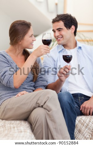 Portrait of a couple having a glass of red wine in their living room - stock photo