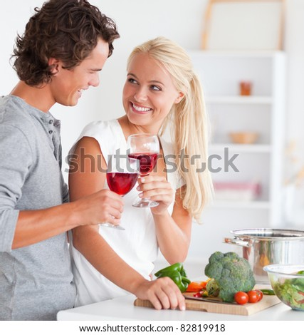 Portrait of a couple having a glass of red wine while cooking - stock photo