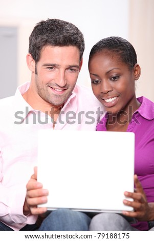 portrait of a couple looking at laptop - stock photo