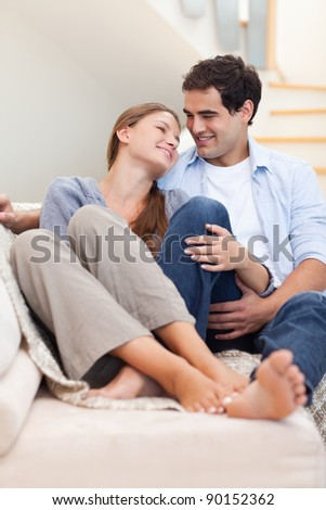 Portrait of a couple lying on a couch while looking at each other - stock photo