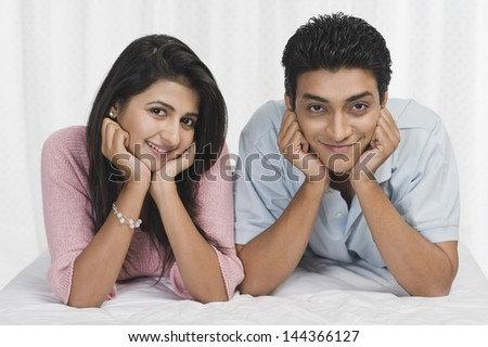 Portrait of a couple lying on the bed and smiling - stock photo