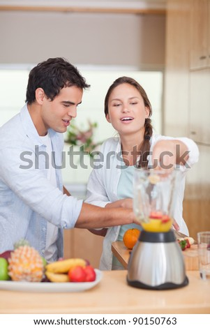 Portrait of a couple making fresh fruits juice in their kitchen - stock photo