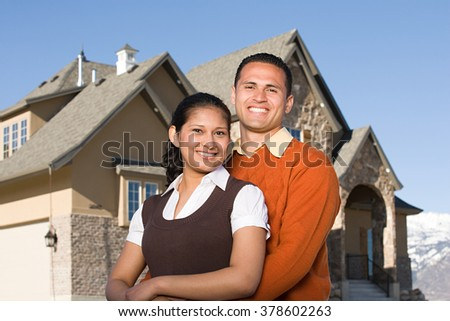 Portrait of a couple outside of a house - stock photo