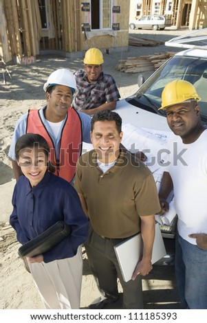 Portrait of a couple with group of architects at construction site - stock photo